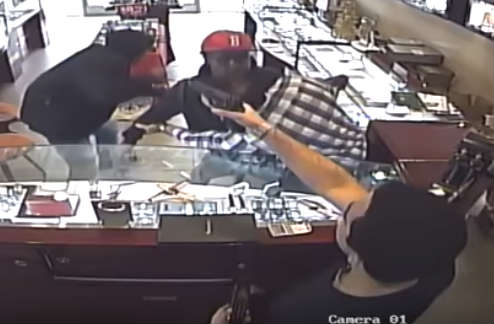 Store owner's nephew grabs a handgun and points it at the culprits. Video surveillance shows one of the suspects ducking, before running out of the store.