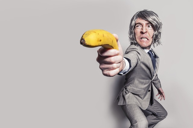 Man in suit pulls banana out and points it like a gun.