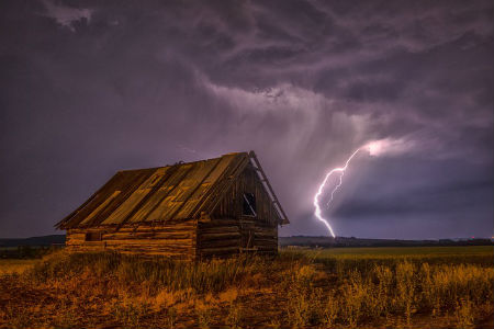 barn under dark clouds with a lightning bolt beside it