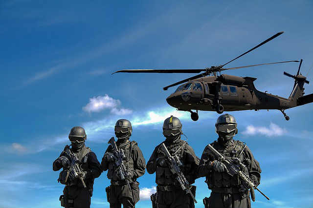 Military police stand in a line as a black helicopter hovers overhead.
