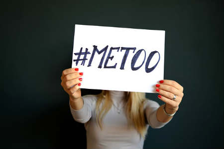 "A woman holds ""me too"" sign"
