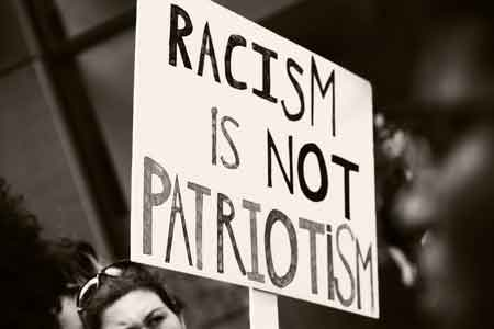 "Sign says, ""Racism is not patriotism""."