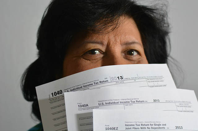 woman hiding behind income tax forms