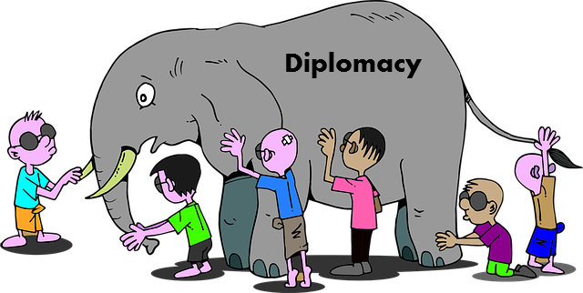 "blindfolded boys feel around on different parts of an elephant which is labeled with the word ""diplomacy"""